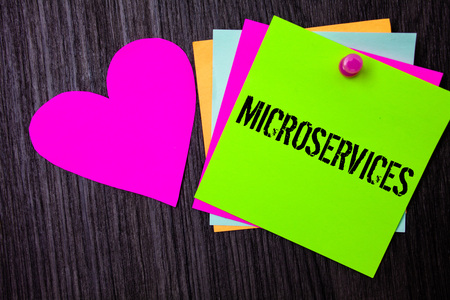Conceptual hand writing showing Microservices. Business photo text Software development technique Decomposing an application Pinned multi colour cards heart polish dark lining background