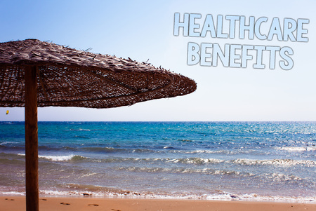 Writing note showing  Healthcare Benefits. Business photo showcasing it is insurance that covers the medical expenses Blue beach sand message idea sunshade water sky natural landscape