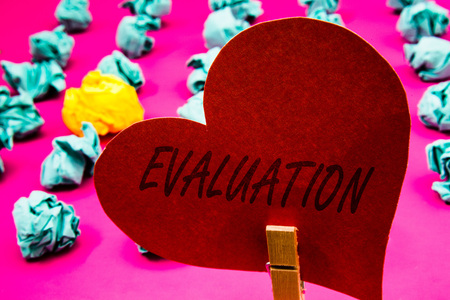 Handwriting text Evaluation. Concept meaning Judgment Feedback Evaluate the quality performance of something Clothespin holding red heart paper crumpled papers ideas mistakes trials Stock Photo
