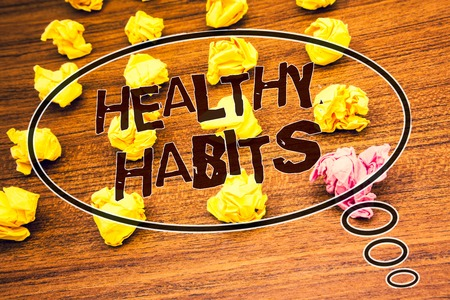 Word writing text Healthy Habits. Business concept for Good nutrition diet take care of oneself Weight Control Text wood desk crumbled paper notes yellow pink stress studying school