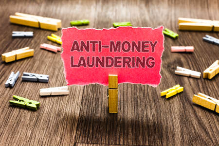 Conceptual hand writing showing Anti Money Laundering. Business photo text stop generating income through illegal actions Clips spread woody table learn study things class schooling