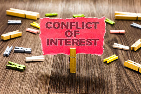Conceptual hand writing showing Conflict Of Interest. Business photo text disagreeing with someone about goals or targets Clips spread woody table learn study things class schooling