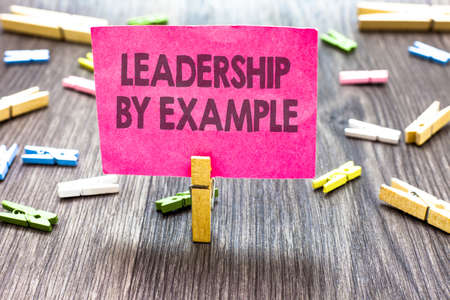 Writing note showing Leadership By Example. Business photo showcasing Becoming role model for people Have great qualities Multiple clips woody table small card clipped notice announcement Banque d'images
