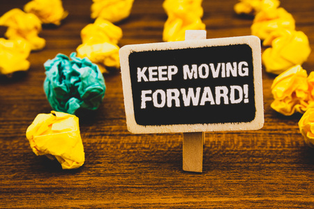 Text sign showing Keep Moving Forward Motivational Call. Conceptual photo Optimism Progress Persevere Move Blackboard with letters wooden floor blurry yellow paper lumps green lob Stock Photo