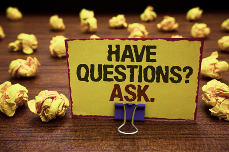 Handwriting text writing Have Questions question Ask.. Concept meaning asking someone respond you with feedback Yellow sticky card clipped text notice crumpled paper balls wood table