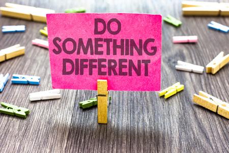 Schrijfbriefje met Do Something Different. Zakelijke foto presentatie wees uniek Denk buiten de doos Veel plezier Meerdere clips houten tafel kleine kaart geknipte aankondiging aankondiging