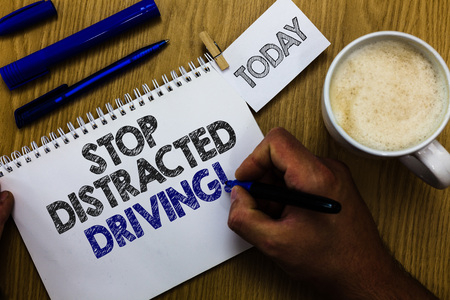 Text sign showing Stop Distracted Driving. Conceptual photo asking to be careful behind wheel drive slowly Man holding marker notebook clothespin reminder wooden table cup coffee Stockfoto