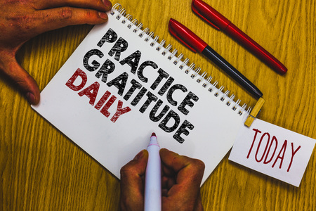 Writing note showing Practice Gratitude Daily. Business photo showcasing be grateful to those who helped encouarged you Man holding marker notebook clothepin reminder wooden table cup coffee