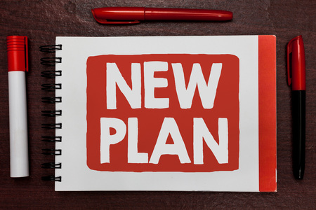 Text sign showing New Plan. Conceptual photo Start of a detailed proposal of doing or achieving something Important ideas highlighted notebook markers wooden table reminder message Фото со стока