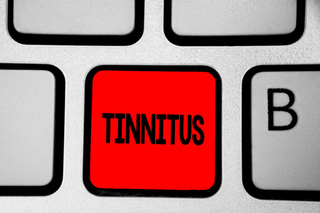 Writing note showing Tinnitus. Business photo showcasing A ringing or music and similar sensation of sound in ears Keyboard red Intention create computer computing reflection document
