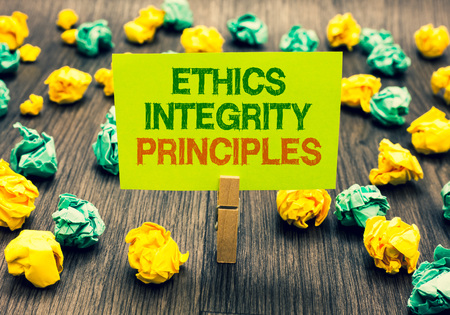 Word writing text Ethics Integrity Principles. Business concept for quality of being honest and having strong moral Clothespin holding yellow note paper crumpled papers several tries mistakes 스톡 콘텐츠