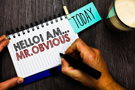 Word writing text Hello I Am.. Mr.Obvious. Business concept for introducing yourself as pouplar or famous person Man holding marker notebook clothespin hold reminder coffee cup wood table