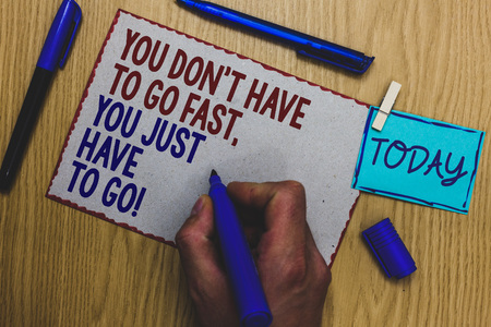 Conceptual hand writing showing You Don t not Have To Go Fast, You Just Have To Go. Business photo text just start to reach Man holding marker paper clothespin express ideas wooden table
