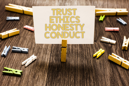 Text sign showing Trust Ethics Honesty Conduct. Conceptual photo connotes positive and virtuous attributes Clothespin holding white paper note several clothespins wooden floor