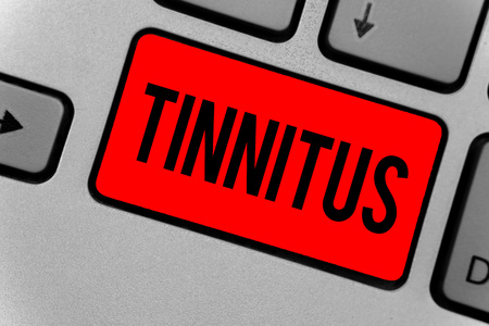 Text sign showing Tinnitus. Conceptual photo A ringing or music and similar sensation of sound in ears Keyboard red key Intention create computer computing reflection document Stock Photo