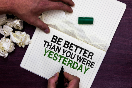 Text sign showing Be Better Than You Were Yesterday. Conceptual photo try to improve yourself everyday Man holding marker notebook page crumpled papers several tries mistakes Stock Photo