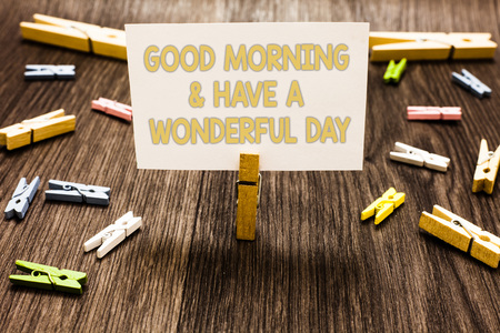 Text sign showing Good Morningand Have A Wonderful Day. Conceptual photo greeting someone in start of the day Clothespin holding white paper note several clothespins wooden floor