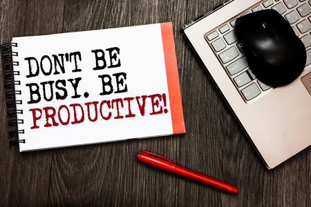 Conceptual hand writing showing Don t not Be Busy. Be Productive. Business photo showcasing Work efficiently Organize your schedule time Bluetooth mouse on keyboard words red pen on wooden deck Imagens