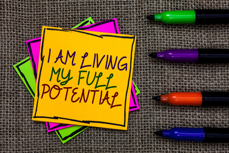 Text sign showing I Am Living My Full Potential. Conceptual photo Embracing opportunities using skills abilities Written on some colorful sticky note 4 pens laid in rank on jute base Archivio Fotografico