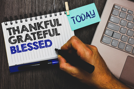 Word writing text Thankful Grateful Blessed. Business concept for Appreciation gratitude good mood attitude Paperclip grip sticky note with text hand hold pen computer on wooden desk Stock Photo