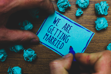 Writing note showing We Are Getting Married. Business photo showcasing Engagement Wedding preparation Loving couple Foggy hand hold marker drawn blue notepad paper lump on wooden floor
