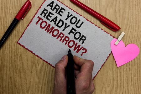 Text sign showing Are You Ready For Tomorrow question. Conceptual photo Preparation to the future Motivation Written sticky note clip pinch heart hand hold marker red pen on wooden desk Stock Photo