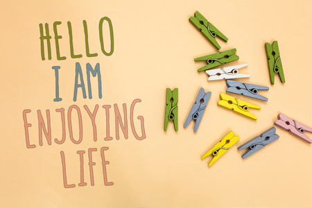 Text sign showing Hello I Am Enjoying Life. Conceptual photo Happy relaxed lifestyle Enjoy simple things Yellow base with painted texts colorful paper clips laid randomly on ground
