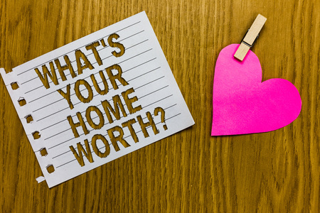 Conceptual hand writing showing What s is Your Home Worth question. Business photo showcasing Value of a house Property Cost Price Rate Yellow woody deck word with white page paper clip grip heart