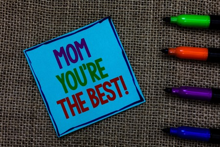 Writing note showing Mom You re are The Best. Business photo showcasing Appreciation for your mother love feelings compliment Blue paper on written letters besides color pens on black sack