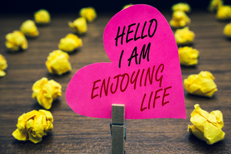 Conceptual hand writing showing Hello I Am Enjoying Life. Business photo text Happy relaxed lifestyle Enjoy simple things Paperclip hold pink written heart woody floor with yellow lobs Imagens