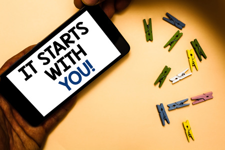 Conceptual hand writing showing It Starts With You. Business photo text Motivation for starting doing something Have discipline Hand holding iPhone with letters and paperclip peach color ground Foto de archivo