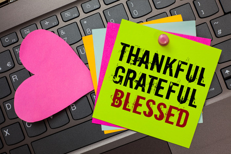 Text sign showing Thankful Grateful Blessed. Conceptual photo Appreciation gratitude good mood attitude Bright colorful written papers pinch by pin pink heart on computer keyboard Stock Photo