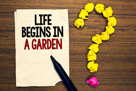 Word writing text Life Begins In A Garden. Business concept for Agriculture Plants growing loving for gardening Written torn page touch black pen yellow paper lob form question on woody deck Фото со стока