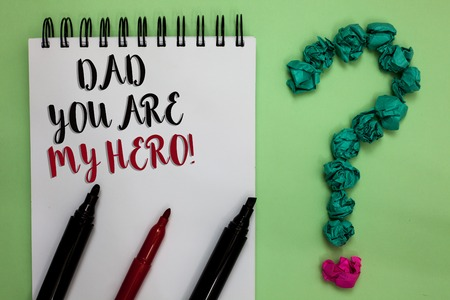 Conceptual hand writing showing Dad You Are My Hero. Business photo showcasing Admiration for your father love feelings compliment Sticky note with texts touch green paper lob question mark