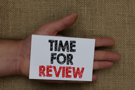 Writing note showing Time For Review. Business photo showcasing Evaluation Feedback Moment Performance Rate Assess Human hand holding white page with black and red color texts on sack