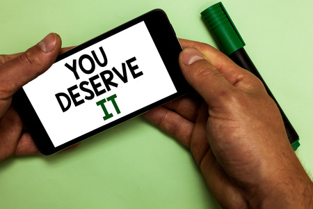 Writing note showing You Deserve It. Business photo showcasing Reward for something well done Deserve Recognition award Human hand hold iPhone with texts touched green marker