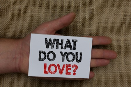 Writing note showing What Do You Love question. Business photo showcasing Enjoyable things passion for something inspiration Human hand holding white page with black and red color texts on sack