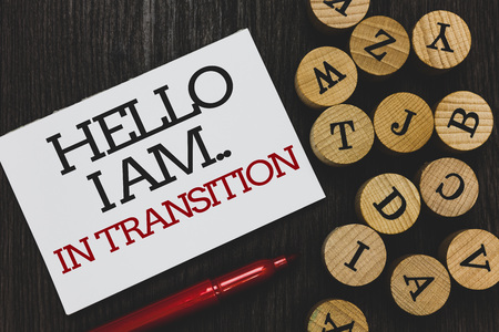 Text sign showing Hello I Am.. In Transition. Conceptual photo Changing process Progressing planning new things Written paper red marker beside round woody alphabets on wooden base