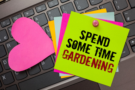 Text sign showing Spend Some Time Gardening. Conceptual photo Relax planting flowers fruits vegetables Natural Bright colorful written papers pinch by pin pink heart on computer keyboard Stock fotó