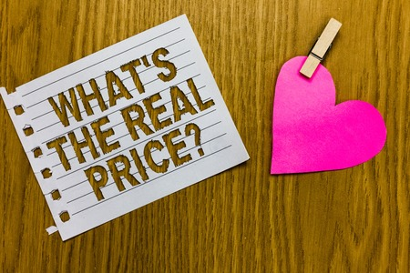 Conceptual hand writing showing What s is The Real Price question. Business photo showcasing Give actual value of property or business Yellow woody deck word with white page paper clip grip heart