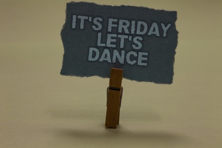 Handwriting text writing It s is Friday Let s is Dance. Concept meaning Celebrate starting the weekend Go party Disco Music Paperclip retain ash color written torn thick page on shadow ash floor Banco de Imagens