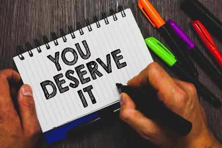 Word writing text You Deserve It. Business concept for Reward for something well done Deserve Recognition award Hand holding pen and paper sketch words near lie some pen on woody desk