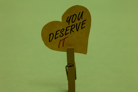 Handwriting text You Deserve It. Concept meaning Reward for something well done Deserve Recognition award Celadon color background paper clip hold love heart for loving with words