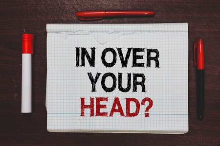 Handwriting text writing In Over Your Head question. Concept meaning To be involved in a difficult situation problem Written black, red words notepad on brown stage white highlighter red pens