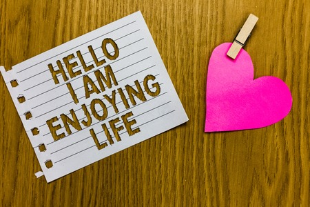 Conceptual hand writing showing Hello I Am Enjoying Life. Business photo showcasing Happy relaxed lifestyle Enjoy simple things Yellow woody deck word with white page paper clip grip heart Imagens
