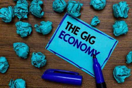Conceptueel handschrift met The Gig Economy. Zakelijke foto presentatie van markt van kortlopende contracten freelance werk tijdelijk blauwe letters geschreven op pagina blauwe marker en papier klonten