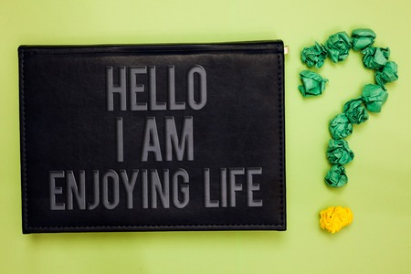 Word writing text Hello I Am Enjoying Life. Business concept for Happy relaxed lifestyle Enjoy simple things Green back black plank with text green paper lob form question mark Imagens