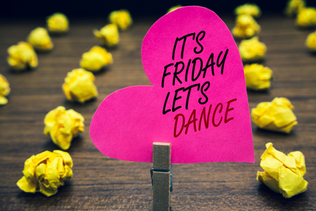 Conceptual hand writing showing It s is Friday Let s is Dance. Business photo text Celebrate starting the weekend Go party Disco Music Paperclip hold pink written heart woody floor with yellow lobs Stock fotó