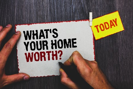 Handwriting text writing What s is Your Home Worth question. Concept meaning Value of a house Property Cost Price Rate Hand grip black marker writing text paperclip stick written page woody deck