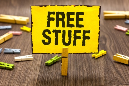 Text sign showing Free Stuff. Conceptual photo Any thing that you can have in a store that is not being paid Clothespin holding yellow paper note several clothespins wooden floor Stockfoto